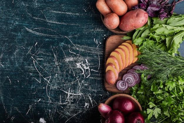 Diverse groenten geïsoleerd op blauwe tafel met kruiden rond. Gratis Foto