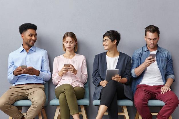Diverse groepen jonge mensen hebben een levendig gesprek terwijl ze in de rij zitten, moderne gadgets gebruiken voor verschillende doelen Gratis Foto