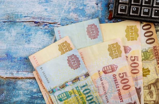 Diverse hongaarse forintbankbiljetten met calculator op lijst in bureau Premium Foto