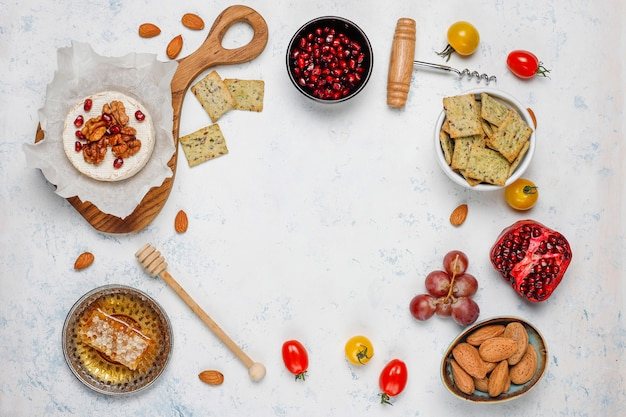 Diverse kaas en kaasplaat op lichte tafel met verschillende noten en fruit Gratis Foto