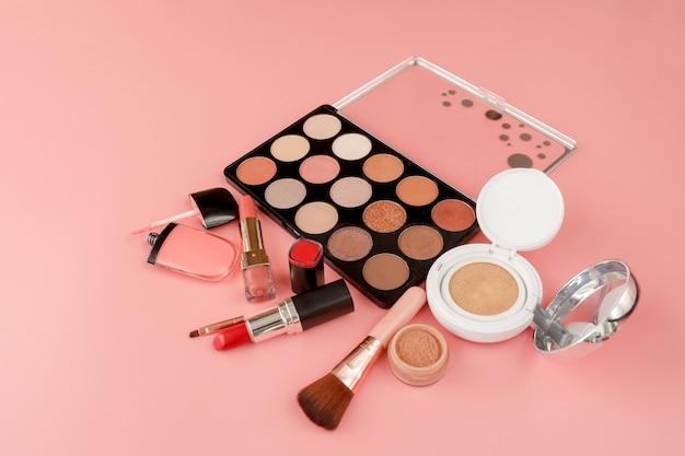 Diverse make-upproducten op roze achtergrond met copyspace Premium Foto