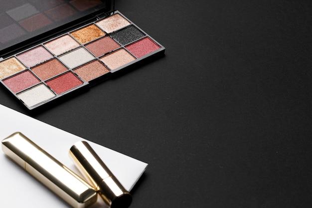 Diverse make-upproducten op zwarte textuurachtergrond. detailopname Premium Foto