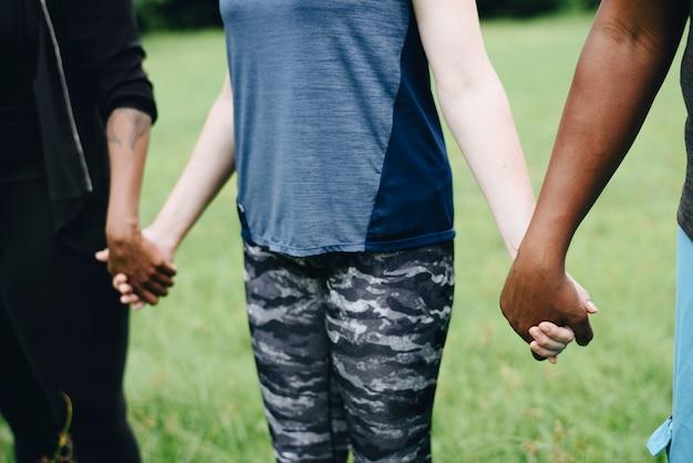 Diverse mensen hand in hand in het park Gratis Foto