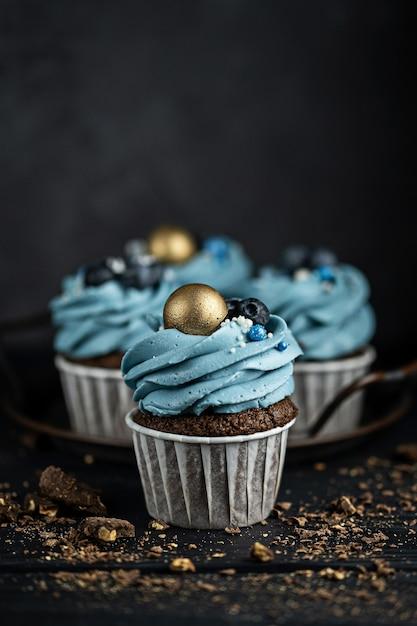 Diverse muffins of cupcakes met blauw gevormde room en met bosbessen op zwarte lijst tegen een donkere achtergrond. rustieke stijl copyspace. Premium Foto