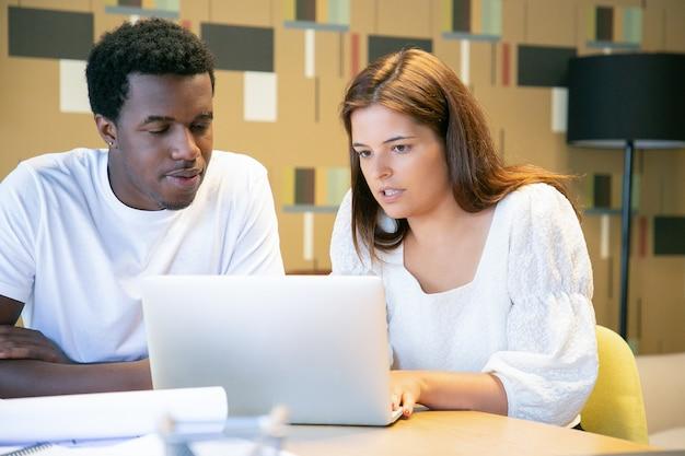 Diverse ontwerpers gericht projectpresentatie op laptop samen kijken, aan tafel zitten en praten, ontwerpproject bespreken Gratis Foto