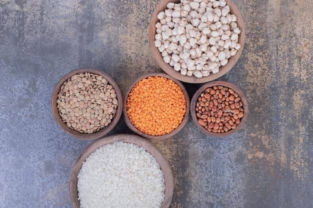 Diverse rauwe bonen, linzen en rijst in houten kommen. Gratis Foto