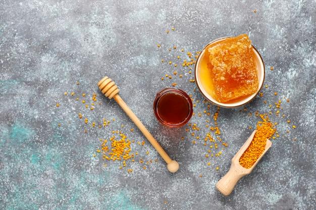 Diverse soorten honing in glazen potten, honingraat en pollen. Gratis Foto