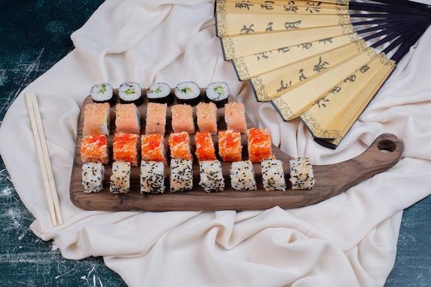 Diverse soorten sushibroodjes die op houten schotel met eetstokjes en japanse ventilator worden gediend. Gratis Foto