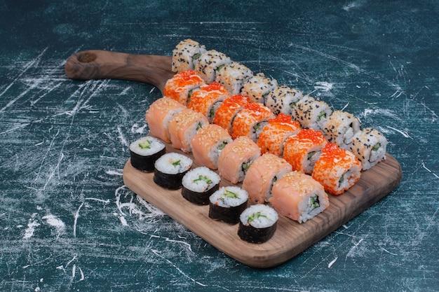 Diverse soorten sushibroodjes die op houten schotel worden gediend. Gratis Foto