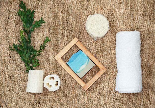 Diverse spa-gerelateerde objecten op stro achtergrond, bovenaanzicht. natuurlijke handgemaakte zeep en accessoires voor lichaamsverzorging. Premium Foto