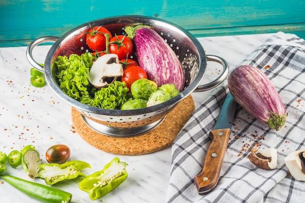Diverse verse groenten in vergiet over marmeren oppervlak Gratis Foto
