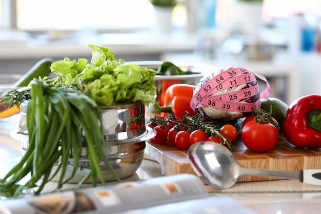 Diverse verse groenten keuken fotografie. sla, rozemarijn en groene ui in steelpan. tomaat en kool verpakt in centimeters op een houten bord. horizontale fotografie van organische ingrediënten Premium Foto