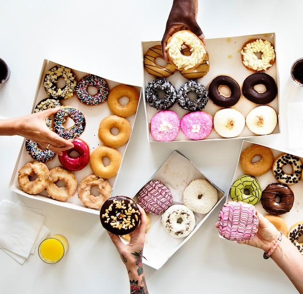 Diversiteit mensen handen bereiken voor donuts Premium Foto