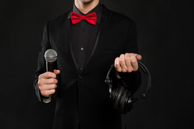 Dj met koptelefoon en microfoon op een zwarte muur Premium Foto