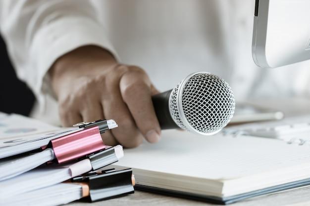 Docent / spreker houd microfoon met papieren document op seminar voor spreken of lezing op klaslokaal universiteit met computer bureaublad op bureau. toespraakconferentie op schoolconcept. vintage toon Premium Foto