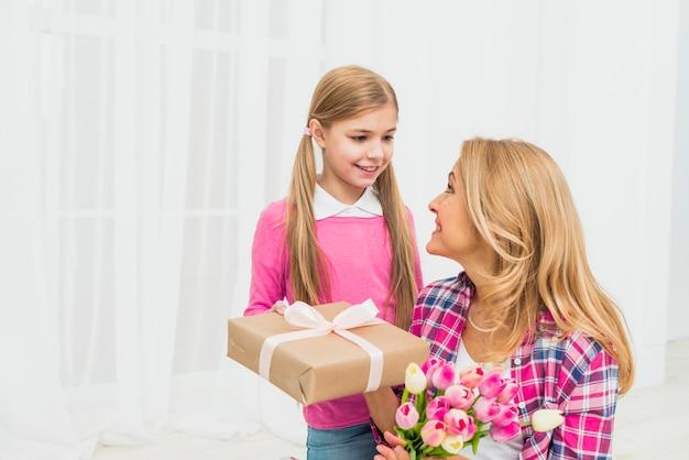 Dochter die gift geeft aan moeder met bloemen Gratis Foto