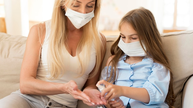Dochter die handdesinfecterend middel geeft aan moeder Gratis Foto
