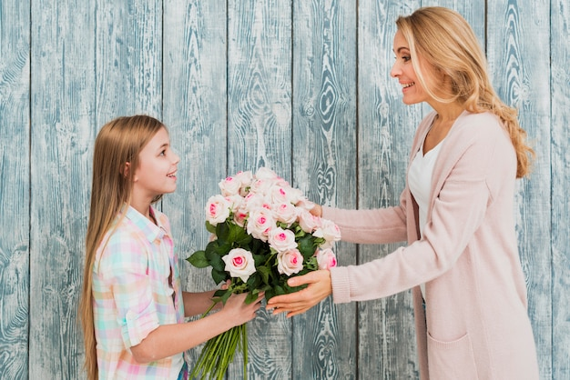 Dochter die moederboeket van rozen voorstelt Gratis Foto