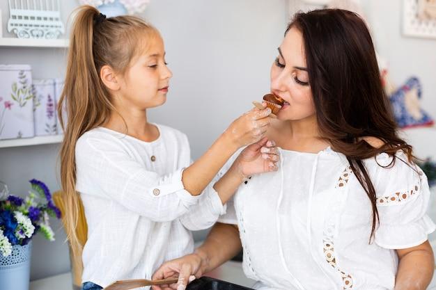 Dochter die muffin aanbiedt aan haar moeder Gratis Foto