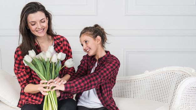 Dochter die witte tulpen geeft aan moeder op laag Gratis Foto