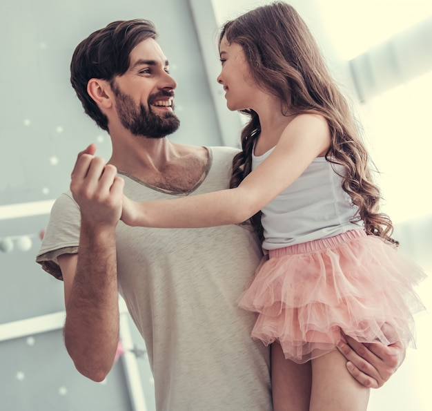 Dochter en haar knappe jonge vader dansen. Premium Foto