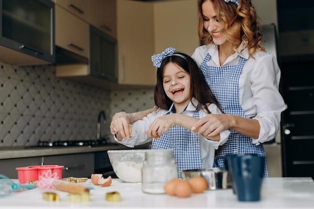 Dochter en haar moeder breken een ei met een glimlach. Premium Foto