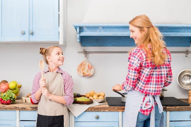 Dochter en haar moeder die voedsel in de keuken koken Gratis Foto
