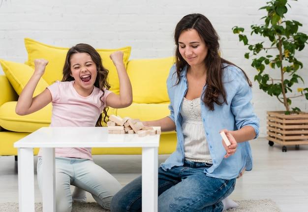 Dochter en haar moeder spelen samen een houten torenspel Gratis Foto