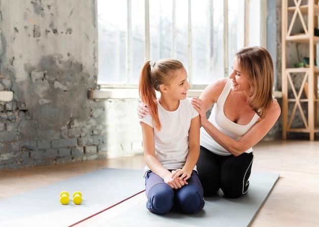 Dochter en moeder kijken elkaar op yogamatten Gratis Foto