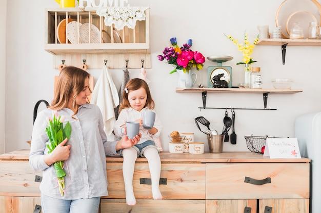 Dochter en moeder met bloemen die thee drinken Gratis Foto