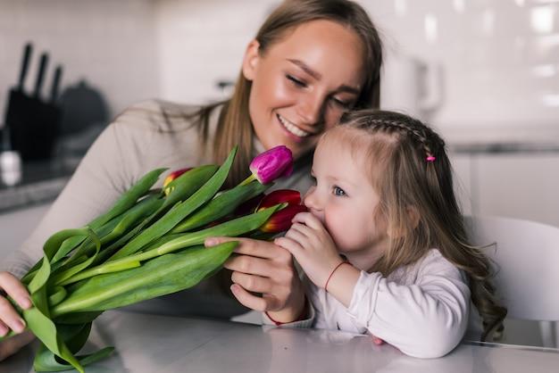Dochter feliciteert moeder en geeft haar bloemen tulpen Gratis Foto