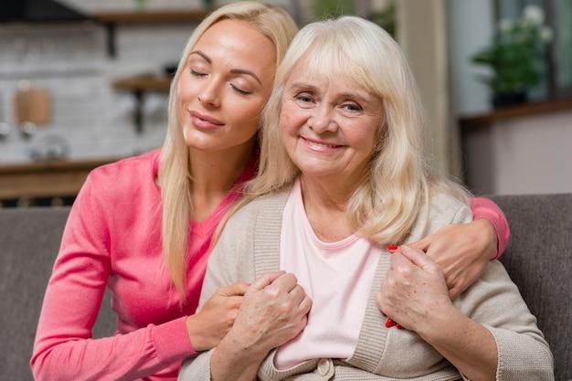 Dochter haar moeder knuffelen en zittend op een bank Gratis Foto