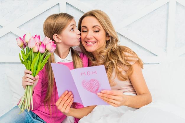 Dochter kussende moeder met groetkaart Gratis Foto