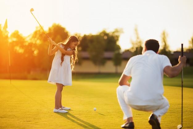 Dochter leert om te golfen geschoten gelukkig gezin. Premium Foto
