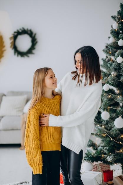 Dochter met moeder bij de kerstboom Gratis Foto