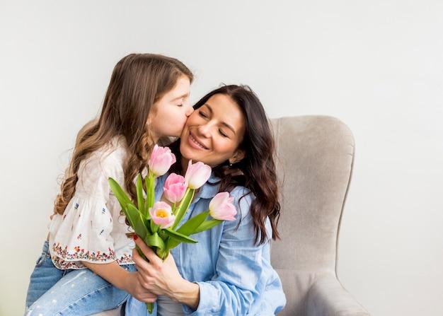 Dochter met tulpen die moeder op wang kussen Gratis Foto