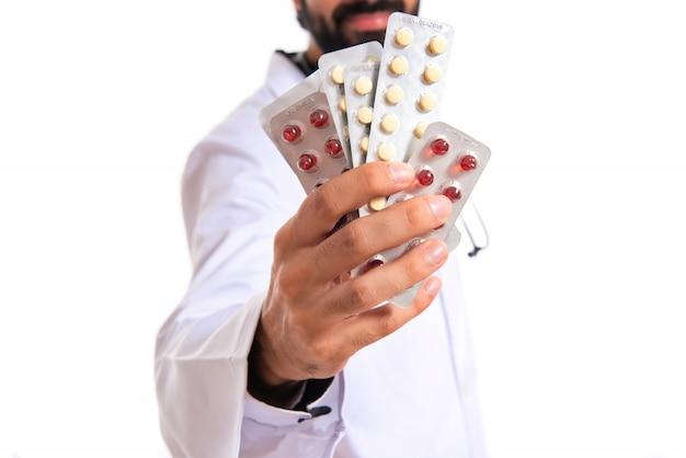 Doctor bedrijf pillen over witte achtergrond Gratis Foto
