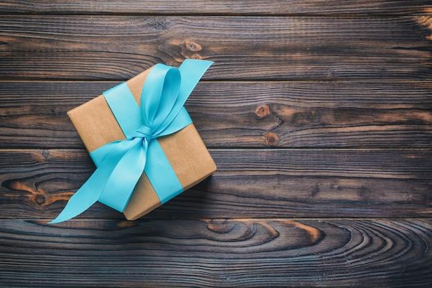 Document giftvakje met blauw lint op donkere houten achtergrond. bovenaanzicht Premium Foto