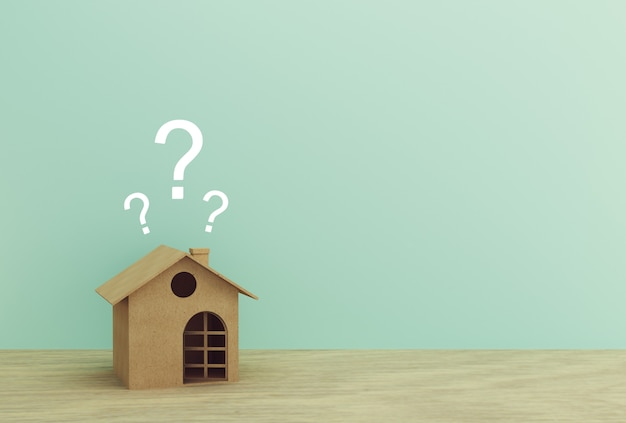Document huismodel met vraagtekens op houten lijst met blauw. copyspace. Premium Foto