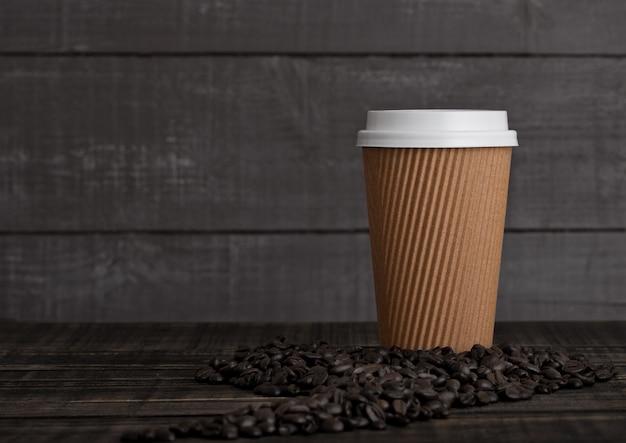 Document koffiekop met cappuccino en koffiebonen op houten achtergrond Premium Foto