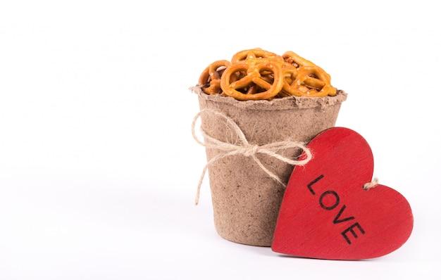 Document kop met zoute crackers en rood houten hart op witte achtergrond. Premium Foto