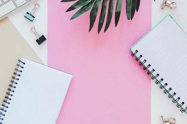Documenten en notitieblokken in de buurt van palmbladeren en toetsenbord Gratis Foto