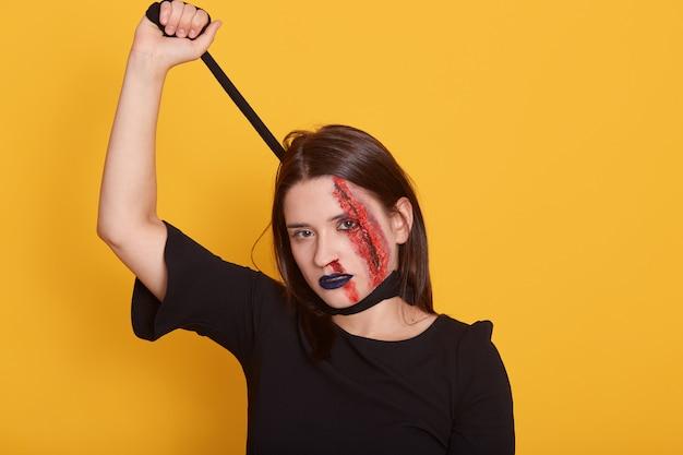 Dode zombie-vrouw klaar voor halloween-feest, gekleed in zwarte jurk en enge make-up, verstikking zichzelf met een stuk stof Gratis Foto