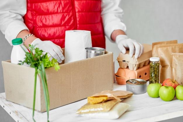 Doe vrijwilligerswerk met chirurgische handschoenen en doe voedsel in de donatiebox Premium Foto
