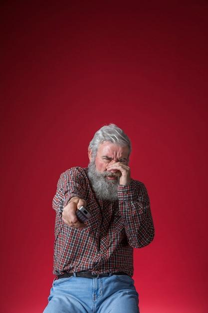 Doen schrikken hogere mens het letten op verschrikkingsfilm op tv die afstandsbediening houden tegen rode achtergrond in hand Gratis Foto