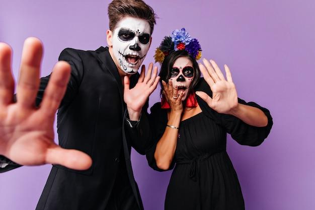 Doen schrikken jonge mensen in halloween-kleding die zich op purpere achtergrond verenigen. binnenfoto van een enthousiast europees stel dat ronddoolt in muertos-kostuums. Gratis Foto