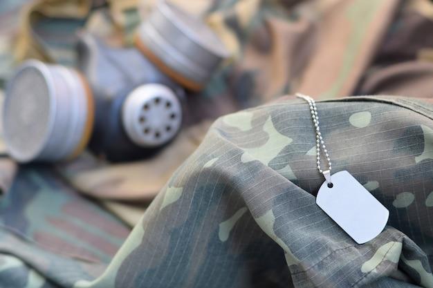 Dog tag met stalker soldaten sovjet gasmasker ligt op groene kaki camouflage jassen Premium Foto