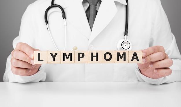 Dokter houdt houten blokjes in zijn handen met tekst lymfoom Premium Foto