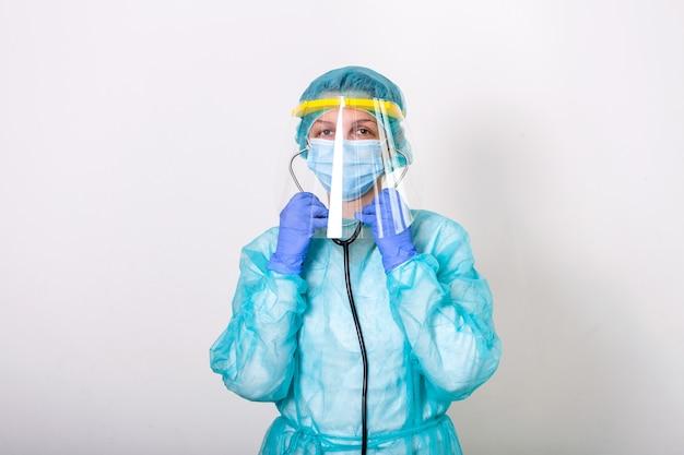 Dokter, verpleegster laten zien hoe u een beschermingspak draagt voor de bestrijding van covid-19 corona-virus met een witte achtergrond. Premium Foto