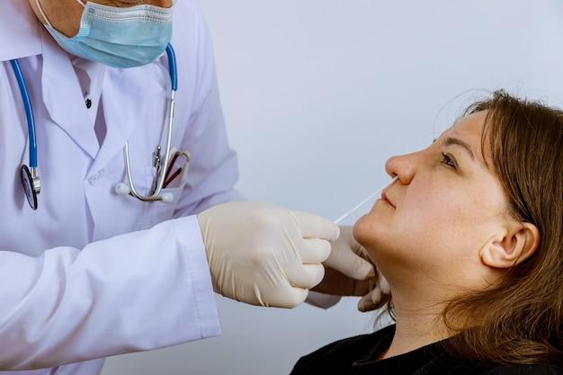 Doktersmedewerker neemt een uitstrijkje een coronavirus covid-19 test een neusmonster voor medisch onderzoek voor in vrouwelijke test Premium Foto